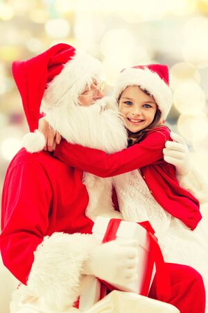children santa claus: holidays, christmas, childhood and people concept - smiling little girl hugging with santa claus over lights background