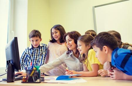 aprendizaje: educación, escuela primaria, el aprendizaje, la tecnología y el concepto de la gente - grupo de niños de la escuela con el maestro en busca de monitor de la computadora en el aula
