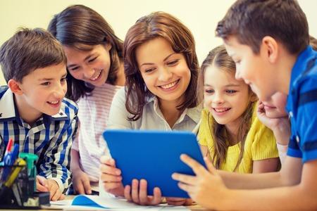 educación, escuela primaria, el aprendizaje, la tecnología y el concepto de la gente - grupo de niños de la escuela con el maestro mira al ordenador Tablet PC en el aula