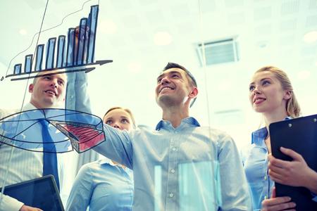 ESTADISTICAS: negocios, personas, trabajo en equipo y la planificación concepto - sonriendo equipo de negocios de dibujo gráfico en el tablón de anuncios de la oficina Foto de archivo