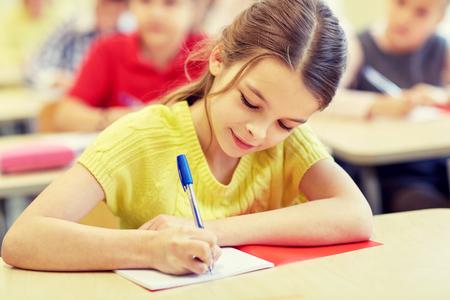 oktatás: oktatás, általános iskola, a tanulás és az emberek koncepciója - csoport iskolás gyerek a toll és jegyzetfüzet írás teszt, osztályterem
