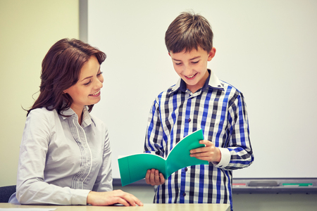 beautiful boy: education, elementary school, learning, examination and people concept - school boy with notebook and teacher in classroom