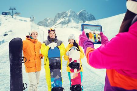 冬のスポーツ、レジャー、友情・人のコンセプト - スノーボードとタブレット pc のコンピューターは、雪と山の背景に写真を撮ると幸せな友達