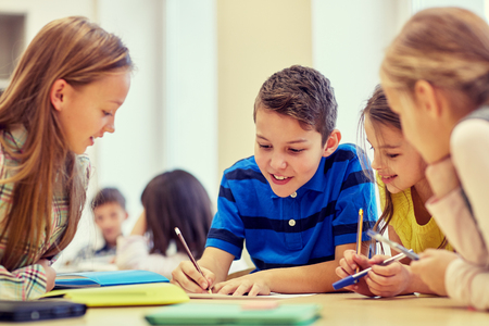 estudiantes: educación, escuela primaria, el aprendizaje y el concepto de la gente - grupo de niños de la escuela con lápices y papeles de escritura en el aula Foto de archivo