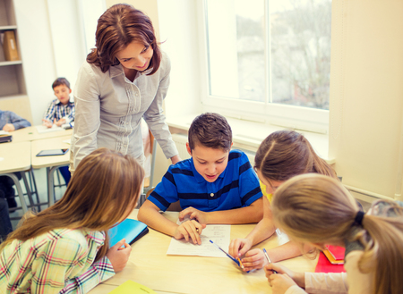 teachers: education, elementary school, learning and people concept - teacher helping school kids writing test in classroom