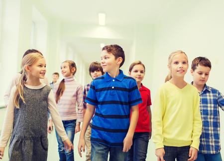 jovenes estudiantes: educación, escuela primaria, las bebidas, los niños y las personas concepto - grupo de niños de escuela sonriente caminando en el pasillo Foto de archivo