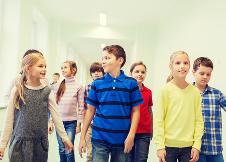 young students: education, elementary school, drinks, children and people concept - group of smiling school kids walking in corridor