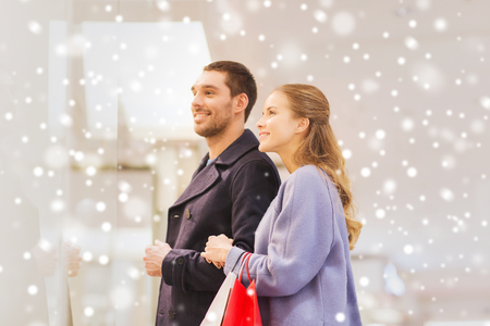 shopper: sale, consumerism and people concept - happy young couple with shopping bags looking to shopwindow in mall with snow effect