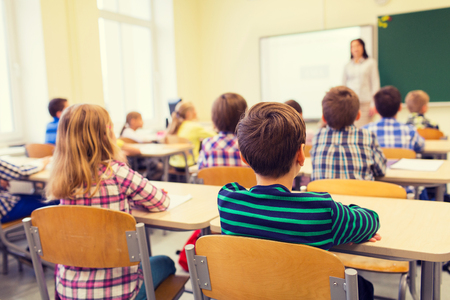 escuela primaria: educación, escuela primaria, el aprendizaje y el concepto de la gente - grupo de niños de la escuela sentarse y escuchar al maestro en el aula de la parte posterior