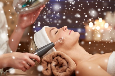 spa woman: people, beauty, spa, cosmetology and technology concept - close up of beautiful young woman lying with closed eyes having face massage by massager and beautician in spa with snow effect