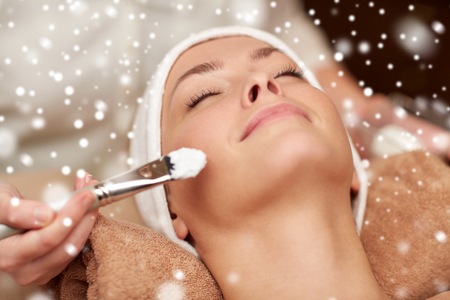 cosmetologies: people, beauty, spa, cosmetology and skincare concept - close up of beautiful young woman lying with closed eyes and beautician hand applying facial mask by brush in spa salon with snow effect Stock Photo