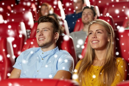 christmas movies: cinema, entertainment and people concept - happy friends or couple watching movie in theater over snowflakes Stock Photo
