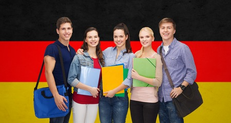 students group: education, learning and people concept - group of smiling students with folders and school bags over german flag background