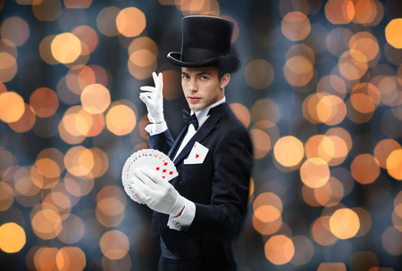 conjuring: magic, performance, gambling, casino, people and show concept - magician in top hat showing trick with playing cards over nigh lights background Stock Photo