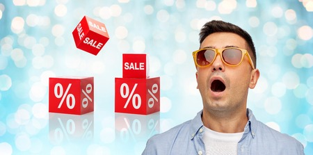 emotional: emotions, shopping, sale, discount and people concept - face of scared or surprised middle aged latin man in shirt and sunglasses over blue holidays lights and red percentage signs background