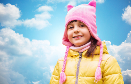 beautiful preteen girl: autumn, childhood, happiness and people concept - happy beautiful little girl portrait outdoors over blue sky and clouds background Stock Photo