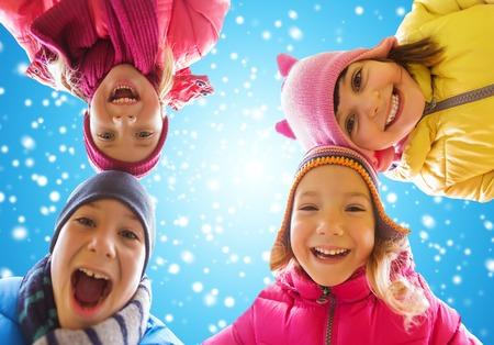 niños felices: la infancia, la amistad, el invierno, la Navidad y la gente concepto - pequeños niños felices se enfrenta al aire libre sobre el cielo azul y el fondo de la nieve Foto de archivo