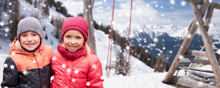 little boys: childhood, winter holidays, friendship and people concept - happy little girl and boy over swing, snow and mountains background