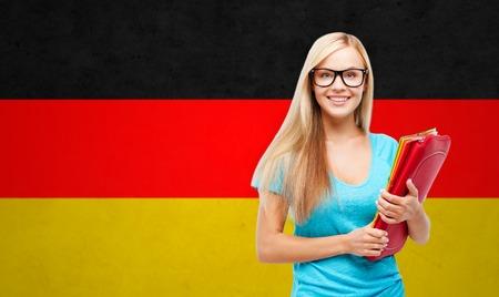 Menschen, Bildung, Lernen und Schule Konzept - glücklich und Teenager-Student Mädchen mit Tablet-PC und Ordner über Deutsch Flagge Hintergrund lächelnd Standard-Bild - 50369696