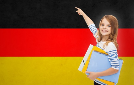 school class: people, education, learning and school concept - happy student girl with folders pointing finger over german flag background