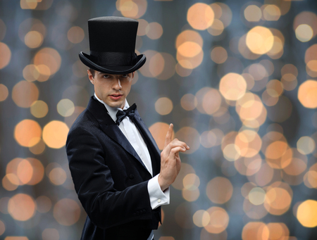 conjuring: magic, performance, circus, show concept - magician in top hat pointing finger up over nigh lights background