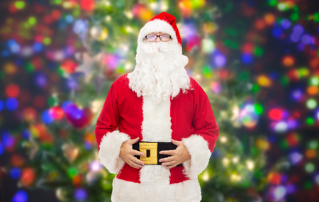 christmas costume: christmas, holidays and people concept - man in costume of santa claus over party lights background