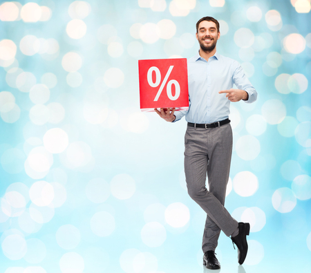 percentage sign: people, sale, shopping, discount and holidays concept - smiling man holding red percentage sign over blue holidays lights background