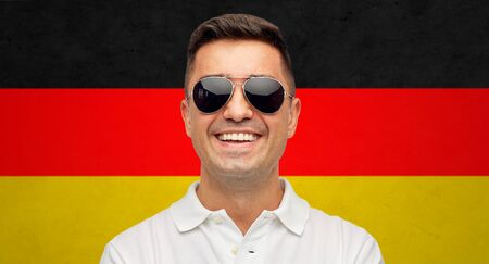 citizenship: summer, accessories, patriotism, citizenship and people concept - face of smiling middle aged latin man in white polo t-shirt and sunglasses over german flag background