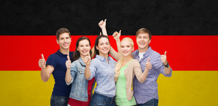 students group: education, nationality, gesture and people concept - group of smiling friends or students standing and showing thumbs up over german flag background Stock Photo