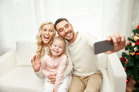 new technologies: christmas, holidays, technology and people concept - happy family sitting on sofa and taking selfie picture with smartphone at home