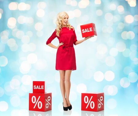 percentage sign: people, shopping, discount and holidays concept - smiling woman in red dress holding cardboard box with sale and percentage sign over blue holidays lights background Stock Photo
