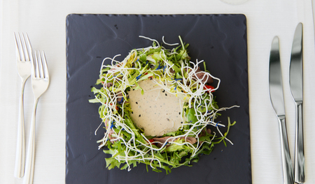 haute: food, culinary, haute cuisine and cooking concept - close up of poultry salad with rice noodles and caesar sauce at restaurant