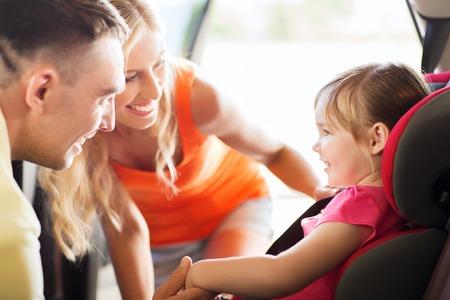 elementos de protecci�n personal: la familia, el transporte, la seguridad, viaje por carretera y la gente concepto - padres felices hablando a la ni�a en el asiento de coche de beb� Foto de archivo