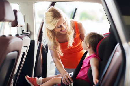 familie, vervoer, veiligheid, weg reis en mensen concept - gelukkige moeder bevestiging kind met autogordel Stockfoto