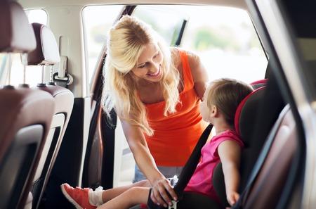 cinturón de seguridad: la familia, el transporte, la seguridad, viaje por carretera y la gente concepto - la madre feliz de fijación niño con el cinturón de seguridad del coche