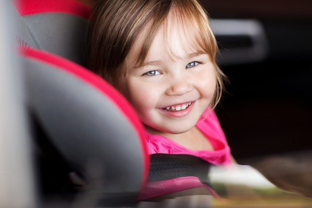 car seat: transport, safety, childhood road trip and people concept - happy little girl sitting in baby car seat