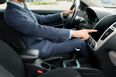 onboard: transport, business trip, technology and people concept - close up of young man in suit driving car and pointing finger to blank black computer screen on dashboard