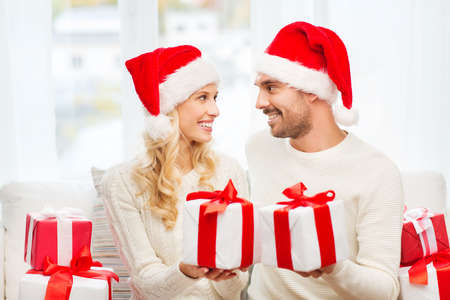 exchanging: christmas, holidays and people concept - happy couple in santa hats exchanging gifts at home
