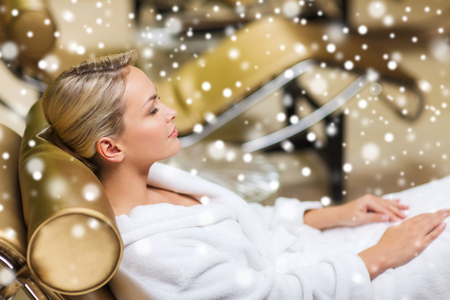 bath robe: people, beauty, healthy lifestyle and relaxation concept - beautiful young woman lying on chaise-longue in bath robe at spa with snow effect