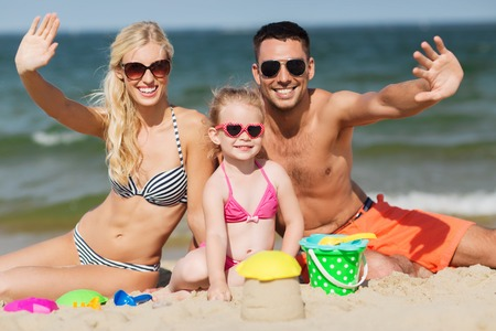 happy life: family, travel, vacation and people concept - happy man, woman and little girl in sunglasses with sand toys waving hands on summer beach Stock Photo