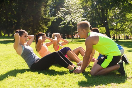 boot camp: fitness, sport, friendship and healthy lifestyle concept - group of happy teenage friends or sportsmen exercising and doing sit-ups at boot camp