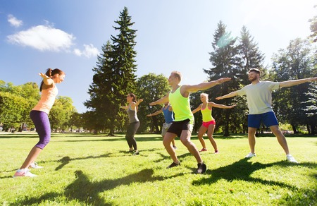 boot camp: fitness, sport, friendship and healthy lifestyle concept - group of happy teenage friends exercising and doing squats at boot camp