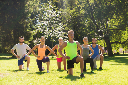 boot camp: fitness, sport, friendship and healthy lifestyle concept - group of happy teenage friends or sportsmen exercising and stretching knee at boot camp Stock Photo