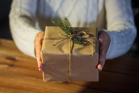 holding close: christmas, holidays, presents, new year and people concept - close up of woman hands holding gift box or parcel wrapped into brown mail paper and decorated with fir brunch Stock Photo