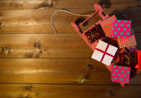 christmas gift box: holidays, christmas, advertisement, new year and celebration concept - close up of many little gift boxes on red wooden sleigh on wooden board