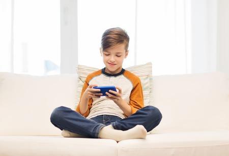 レジャー、子供、技術、インターネット通信、人々 の概念 - スマート フォン携帯メール メッセージを持つ少年を笑ったり、家でゲームをプレイ