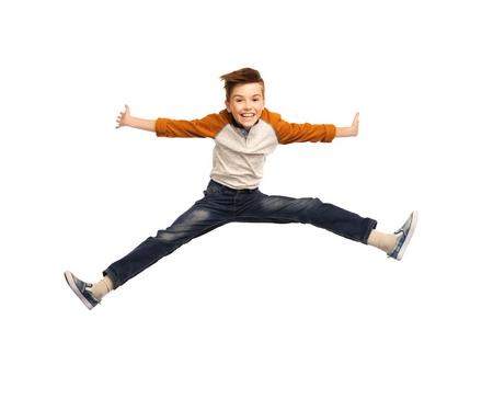 Glück, Kindheit, Freiheit, Bewegung und Menschen Konzept - glücklich lächelnde Junge springt in der Luft