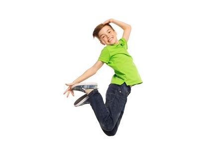 la felicidad, la infancia, la libertad, el movimiento y la gente concepto - sonriente niño saltando en el aire Foto de archivo
