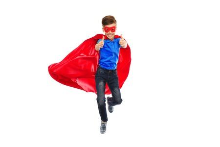 boy jumping: la felicidad, la libertad, la infancia, el movimiento y la gente concepto - muchacho en rojo capa s�per h�roe y m�scara de volar en el aire y que muestra los pulgares para arriba Foto de archivo