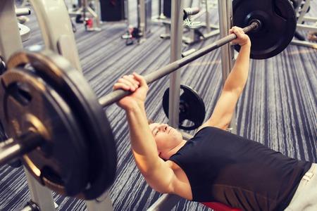 deporte, culturismo, estilo de vida y concepto de la gente - hombre joven con la barra a flexionar los músculos y hacer press de banca en el gimnasio Foto de archivo